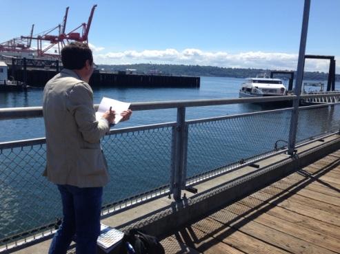 Photo of Seattle Sketcher Gabriel Campanario sketching at Pier 50