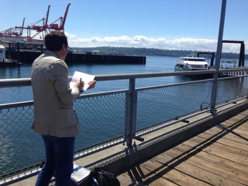 Photo of Seattle Sketcher Gabriel Campanario sketching at Pier 50