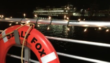 The railing of the Sally Fox is decked in holiday lights, with a Washington State Ferry in the background.