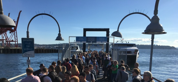 Afternoon commuters of both the King County Water Taxi and Kitsap Transit Fast Ferry crowd Pier 50 in Downtown Seattle.