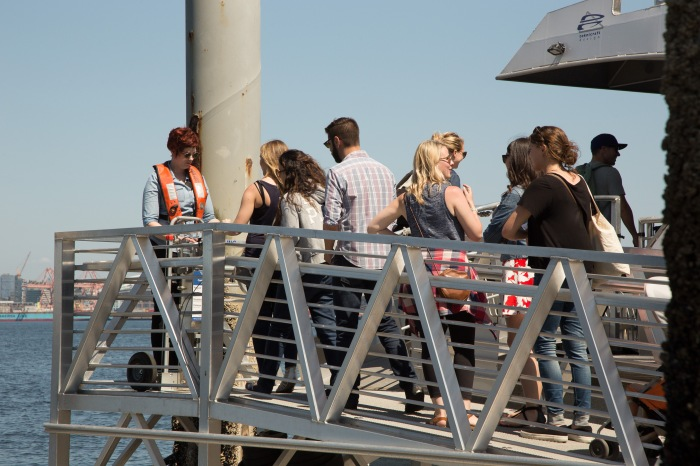 A deckhand scans tickets and passes of riders boarding the West Seattle ferry bound for Downtown Seattle.