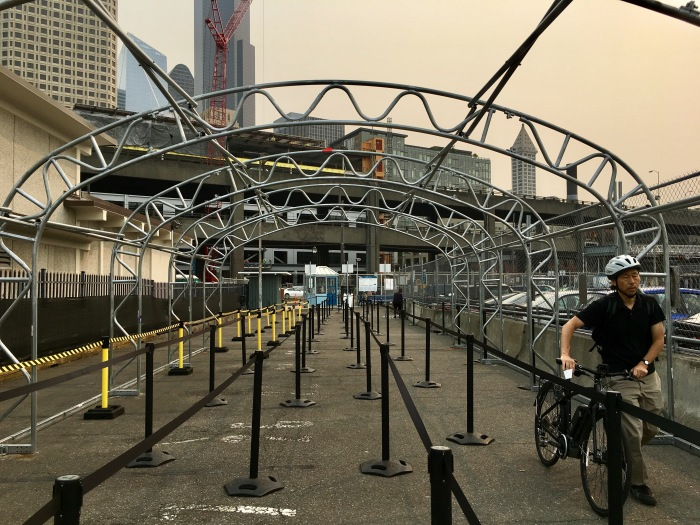 A bike rider bound for West Seattle walks under metal frames at King County Water Taxi's dock that will soon support a canopy to protect riders from the elements.