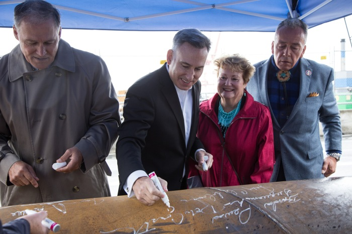 King County Executive Dow Constantine signs a steel pile that will be used to help support the future Colman Dock. To the left is Washington Gov. Jay Inslee, and to the right are state Rep. Judy Clibborn and Bardow Lewis, Vice Chairman of The Suquamish Tribe.