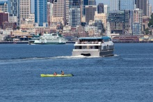 A pair of kayakers glide along Elliott Bay as King County Water Taxi's MV Doc Maynard cuts toward Downtown Seattle.