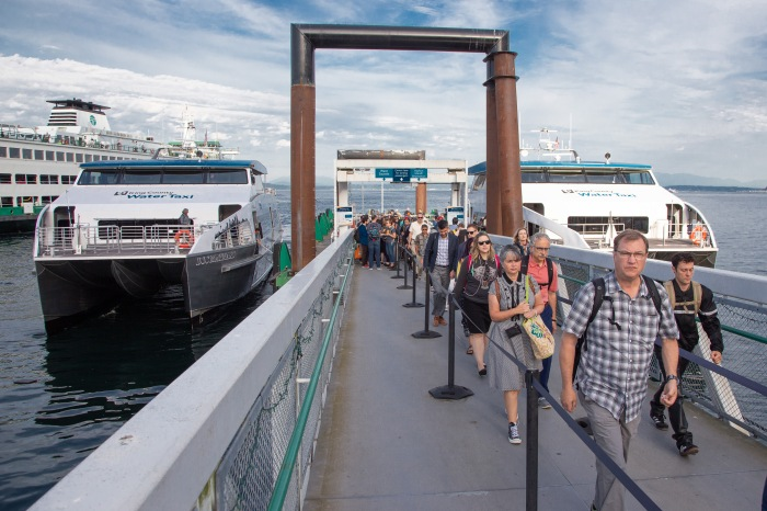 Riders disembark from the MV Doc Maynard on the Seattle waterfront, with the MV Sally Fox positioned on the opposite side of the float.