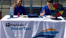 Interns for King County Water Taxi take a break to snap a picture while working the table on the Seattle waterfront.