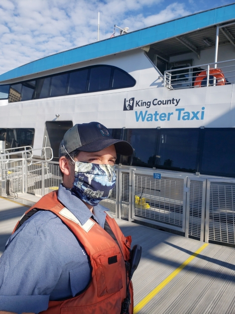 Water taxi crew member dons a a cloth mask