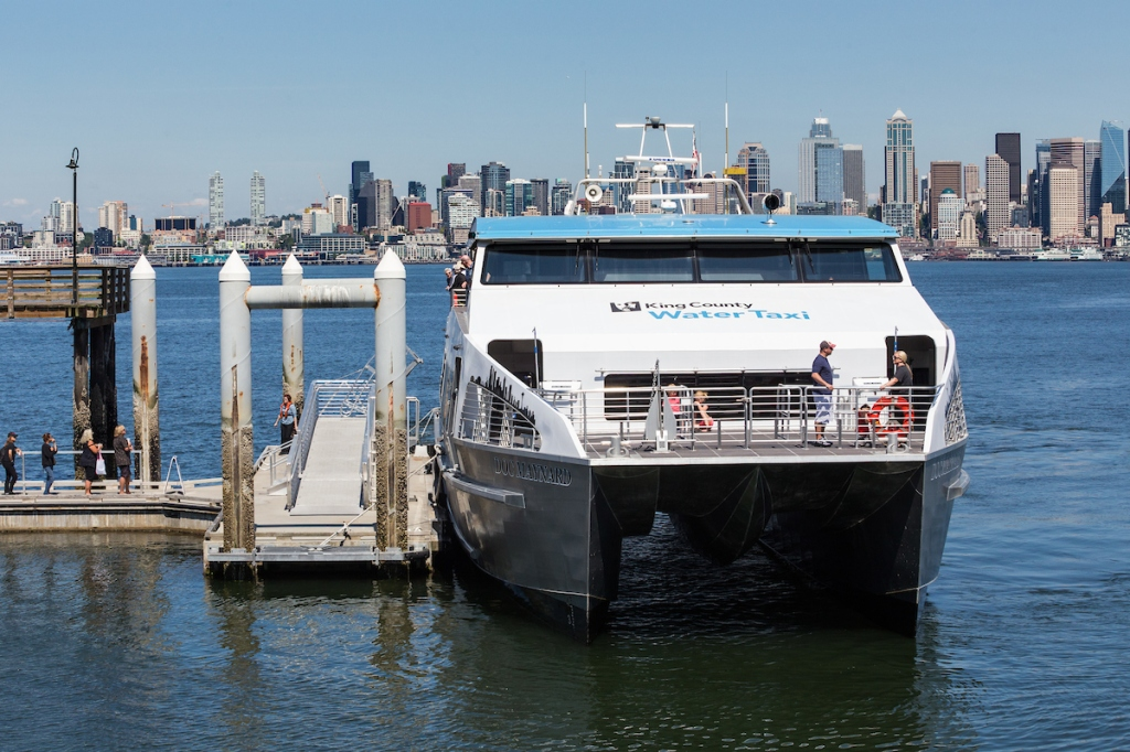 Photo of water taxi at Seacrest Dock in West Seattle on a sunny day, the Seattle skyline in the background.